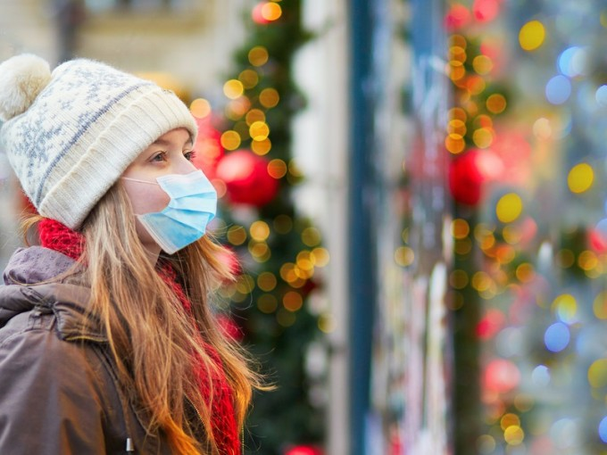 a girl in a mask stares at the window of twinkling lights